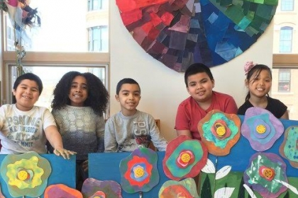 Children posing with handmade flower paintings in front of a color wheel