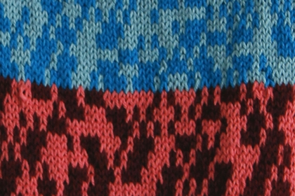 Detail of knitted artwork with bands of red and blue